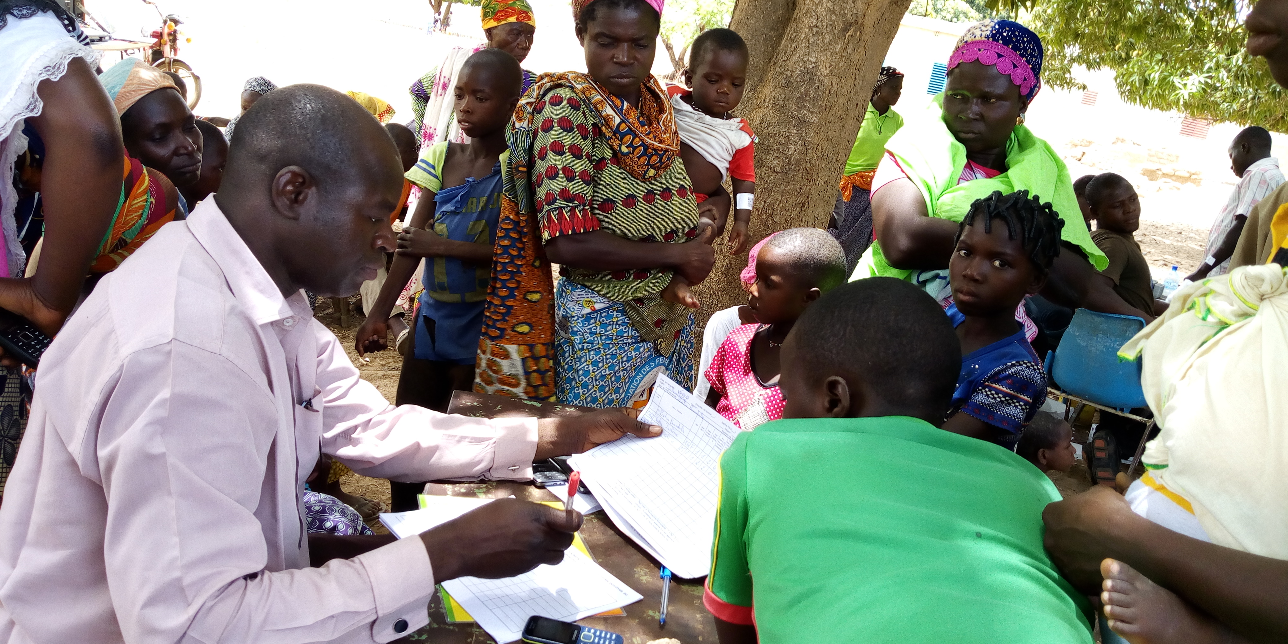 A nurse from the Salembaoré Health and Social Promotion Centre meets with a family during a survey registration session. Photo: Lucien Mano, HKI-Burkina Faso