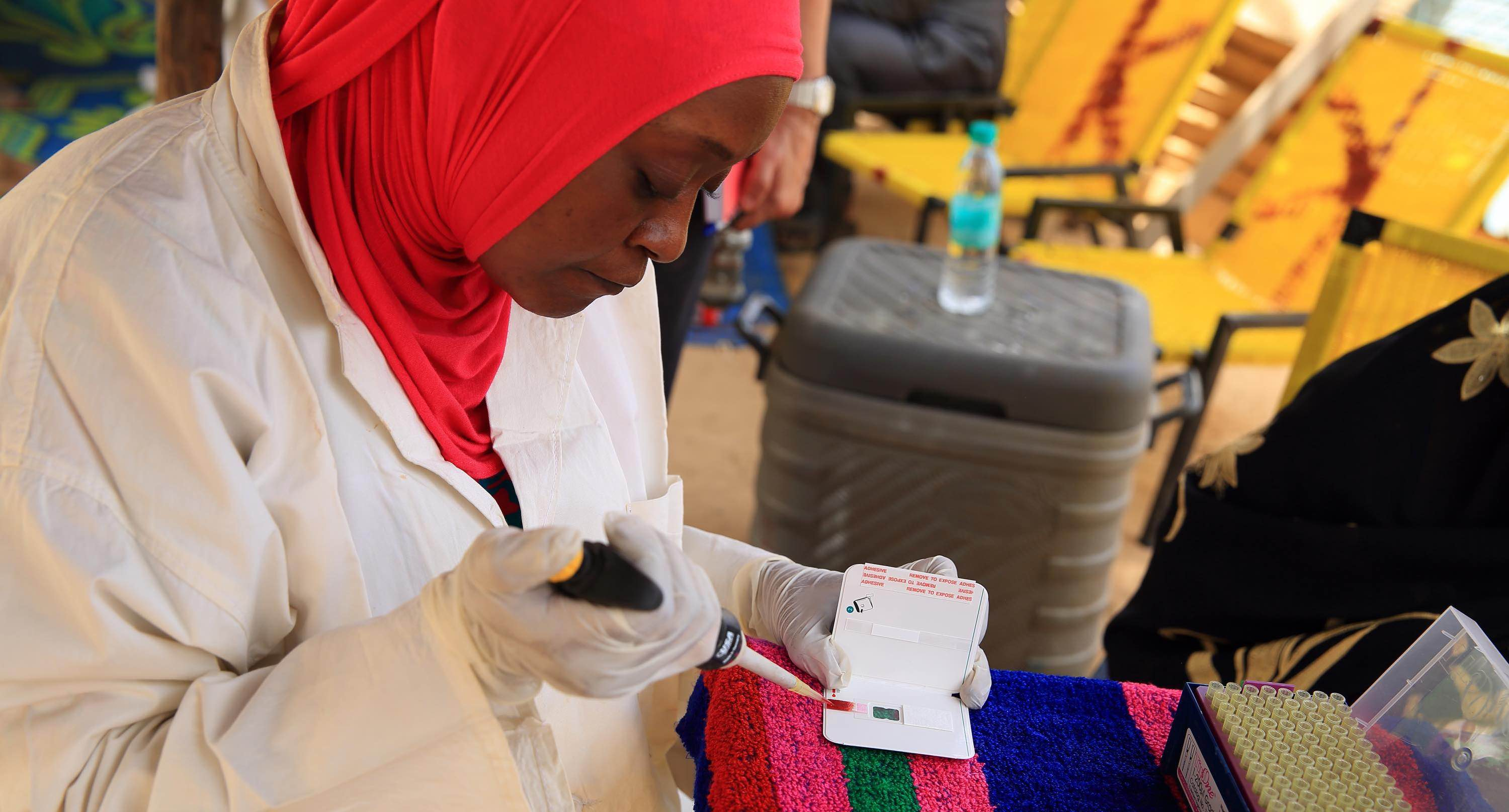 a community health worker gives a child medicaion
