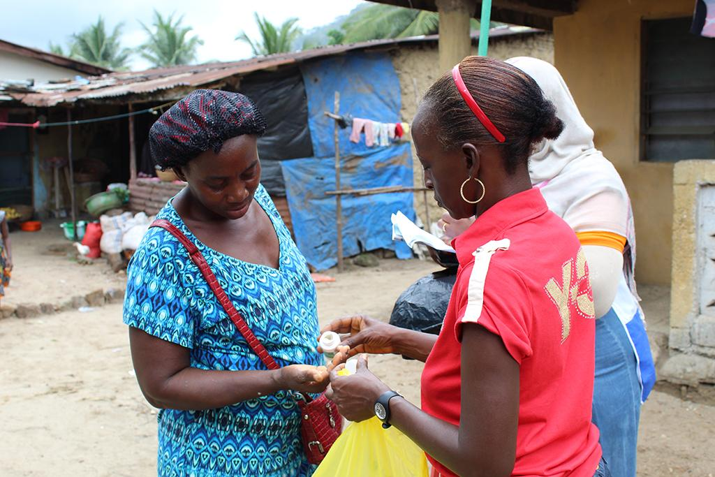 A community health worker gives medication to a community member
