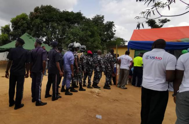 Soldiers and police queue up to take disease-preventing medicine provided with support from USAID's Act to End Neglected Tropical Diseases l West program in Waterloo, Sierra Leone. Photo: Helen Keller International.