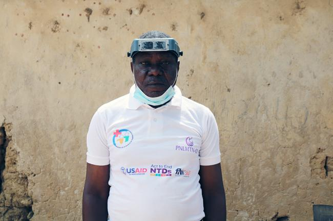 A doctor in Ghana stands against a wall with a face mask tucked under his chin.